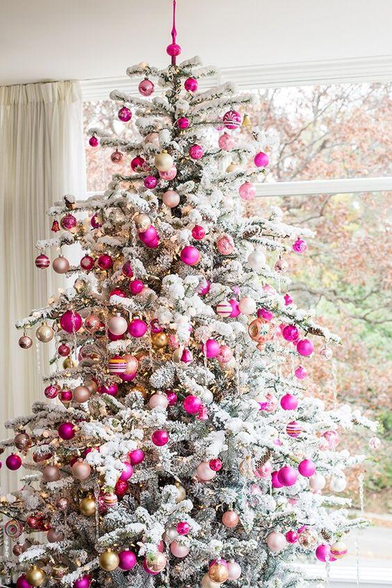 un albero di Natale floccato decorato con decorazioni e luci neutre, rosa caldo e cipria sembra glam, chic e molto moderno