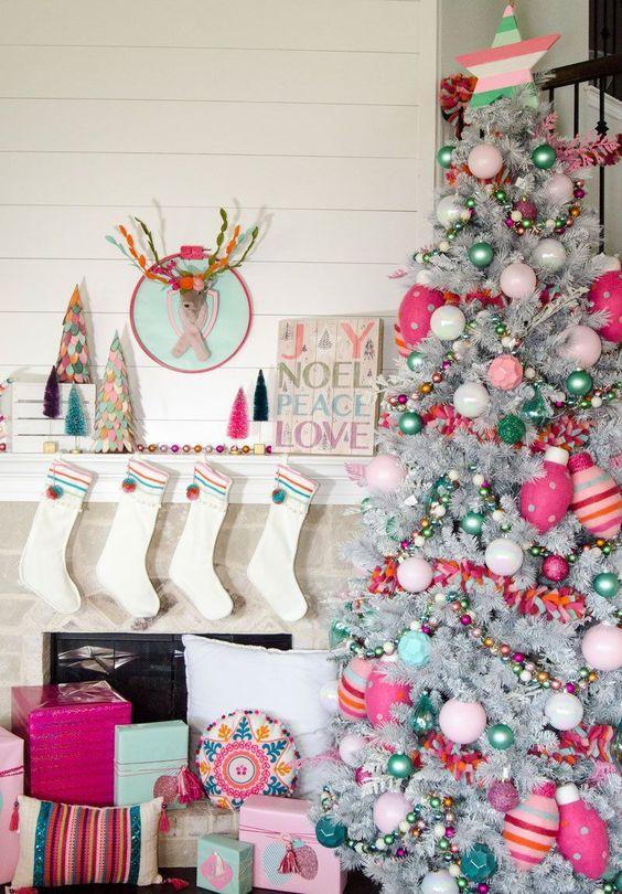 un albero di Natale d'argento luminoso e divertente con ornamenti rosa, rosa caldo e verdi, perline e ornamenti a strisce e stelle