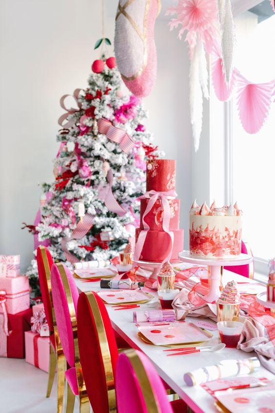 un luminoso spazio natalizio decorato in rosso, rosa e oro, con ventagli di carta, nastri e ornamenti è un'idea audace
