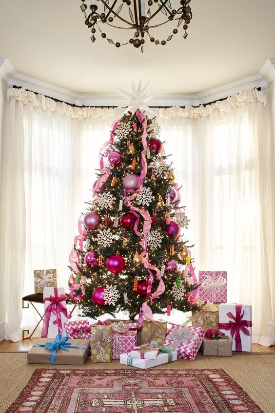 un audace albero di Natale decorato con ornamenti di paillettes rosa e rosa, nastri rosa, luci e grandi fiocchi di neve e una grande stella in cima