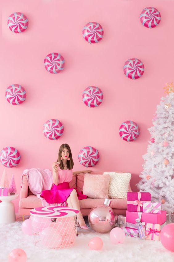 uno spazio per le vacanze rosa con menta piperita sul muro, mobili rosa e palloncini e ornamenti rosa su un albero di Natale bianco