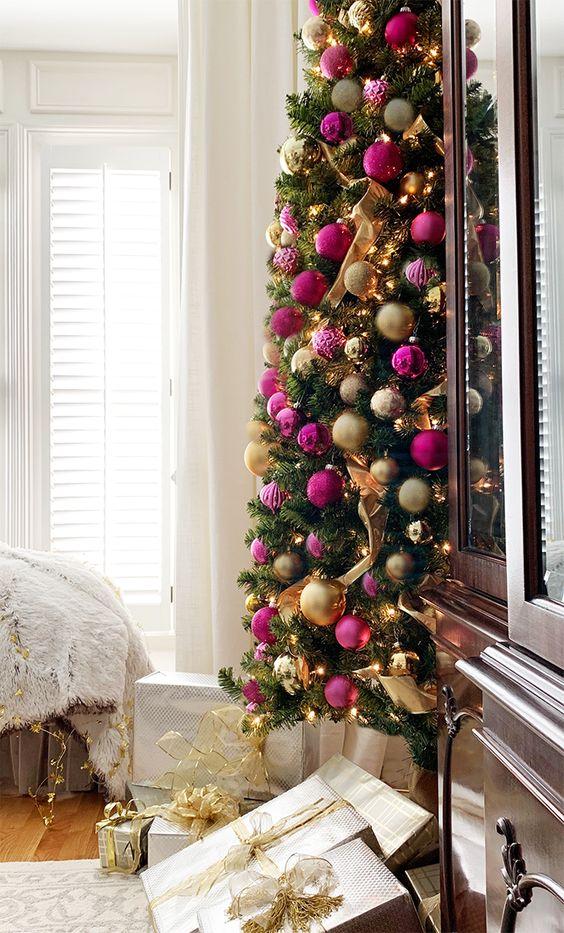 un raffinato albero di Natale con luci, ornamenti e nastri oro e rosa caldo e fucsia è una splendida idea per uno spazio di vacanza chic