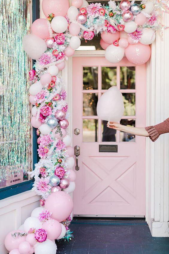 una bella ghirlanda natalizia rosa di palloncini, ornamenti rosa, fiori finti e un po 'di verde è una bella idea