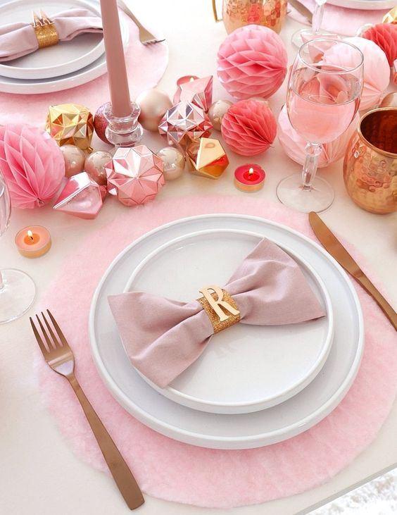 un tavolo da vacanza rosa con caricatori rosa, ornamenti, pompon di carta, bicchieri, candele e tovaglioli più posate opache