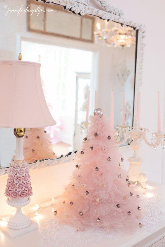 un albero di Natale rosa con volant decorato con piccoli ornamenti metallici aggiunge un tocco glam fresco e chic a questo spazio vintage