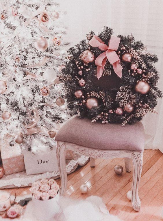una ghirlanda natalizia in abete raffinata e glamour punteggiata di ornamenti rosa e un grande fiocco è un'idea chic per portare un tocco di glamour