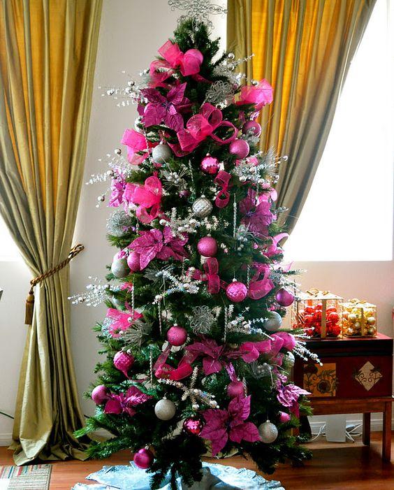 un albero di Natale glam con ornamenti rosa caldo e fucsia e fiori di stoffa, ramoscelli d'argento, perline e luci è un'idea brillante