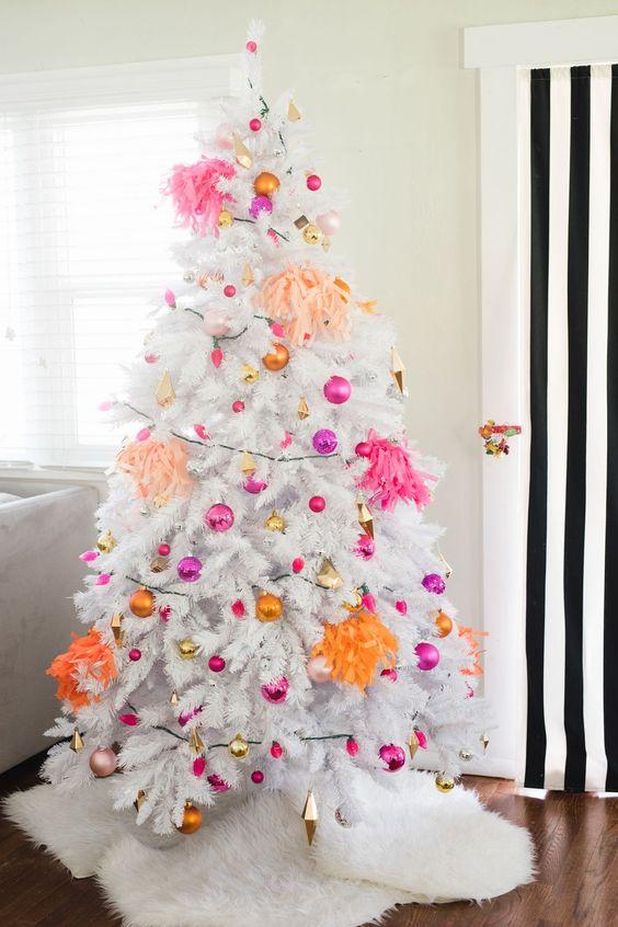 un albero di Natale bianco con ornamenti rosa caldo, fucsia, oro e arancione e nappe luminose è tutto incentrato sull'arredamento moderno e sui colori vivaci