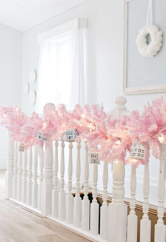 bella decorazione della ringhiera delle vacanze con una ghirlanda di rami di abete rosa, luci e mini case appese sopra è un'idea adorabile