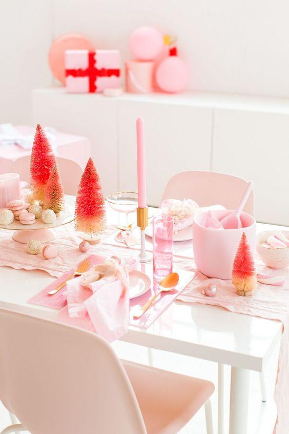 un semplice e moderno paesaggio da tavola di Natale rosa con lenzuola rosa chiaro, candele, caricatori acrilici, ornamenti e alberi di orpelli ombre