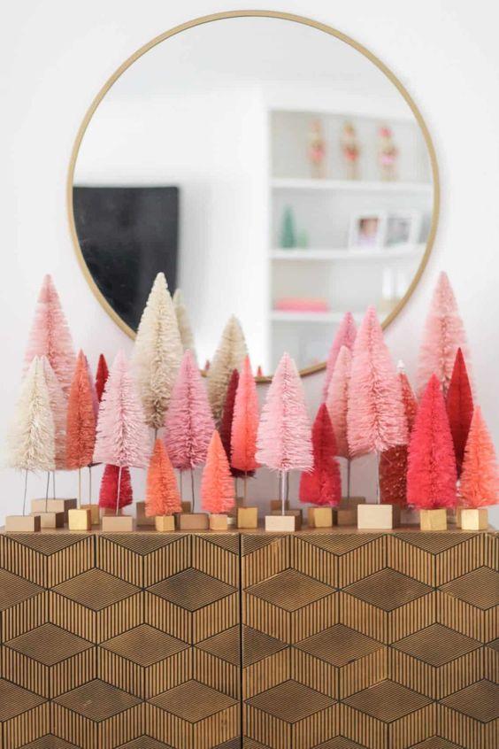 una disposizione di alberi di Natale in orpello corallo e rosa e rosso sulla tua consolle darà un tocco di festa moderna all'ingresso