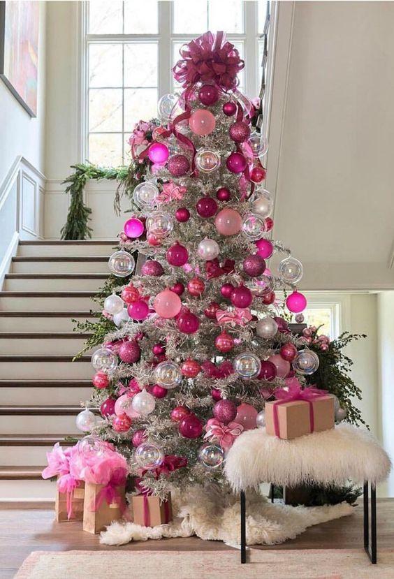 un albero di Natale d'argento decorato con ornamenti rosa, fucsia, trasparenti e argento e un grande fiocco fucsia in cima