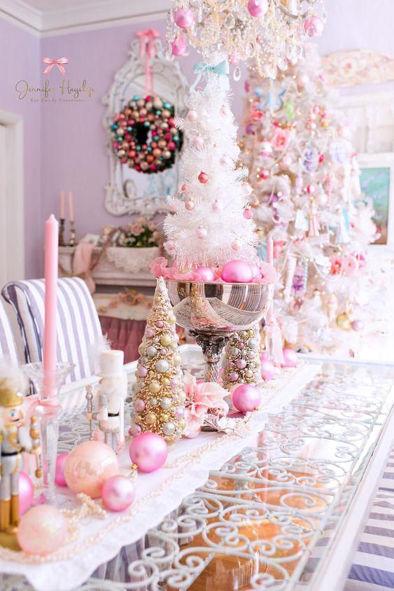 decorazioni natalizie glam con decorazioni e candele color pesca e rosa caldo, perline, ornamenti rosa in una ciotola e un mini albero bianco con decorazioni rosa e blush
