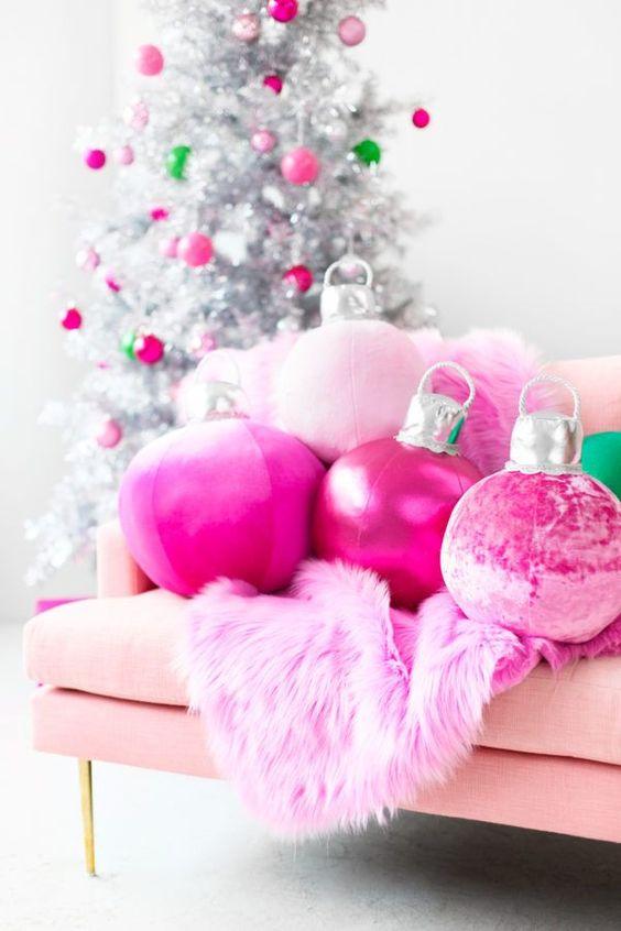 cuscini rosa caldo con ornamenti natalizi e una coperta in pelliccia sintetica più ornamenti coordinati sull'albero di Natale d'argento