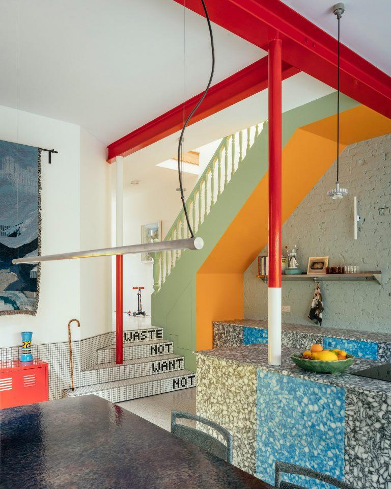 La cucina è grigia e blu e potresti vedere colonne rosse e bianche che aggiungono colore