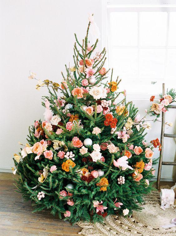 un bellissimo albero di Natale con fiori arancioni, ruggine, bordeaux, blush e rosa, alcuni rami e foglie è un'idea molto carina e romantica