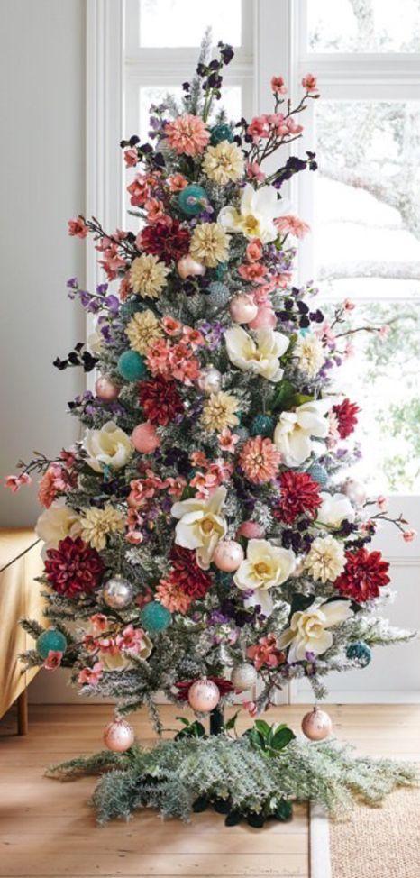 un albero di Natale floccato decorato con fiori e rami fioriti, con ornamenti arrossati e alcune foglie scure sembra adorabile