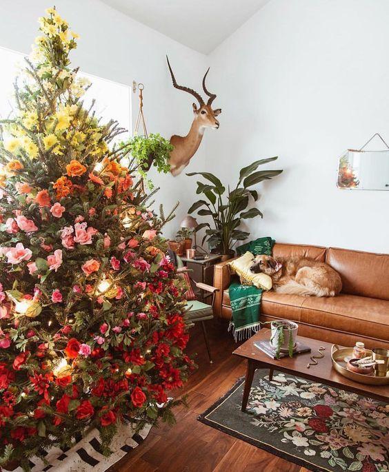 un fantastico albero di Natale sfumato decorato con fiori e foglie gialli, rosa e rossi più luci è adorabile