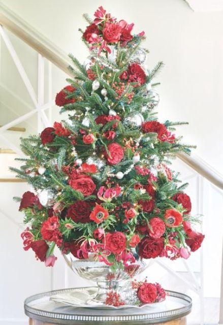 un bellissimo albero di Natale da tavolo con fiori freschi verdi, rossi e bordeaux e alcuni ornamenti d'argento è un'idea elegante