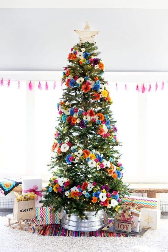 un albero di Natale luminoso con fiori finti arancioni, rosa, blu, bianchi e gialli e un cappello a cilindro in legno è stupendo