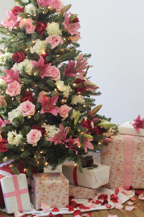un delizioso albero di Natale decorato con luci, fiori bianchi, rosa e bordeaux è un'opzione molto glam e alla moda