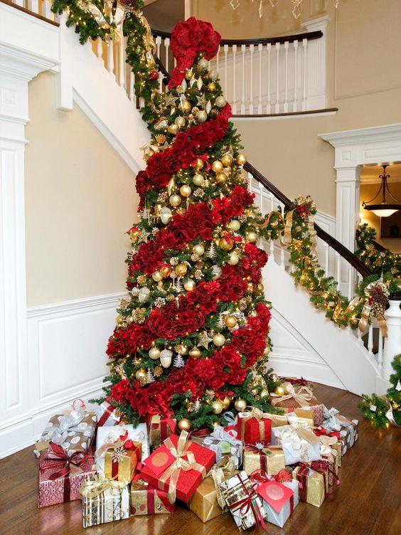 un albero di Natale sbalorditivo decorato con rose rosse e ornamenti d'oro tra le ghirlande floreali è magnifico