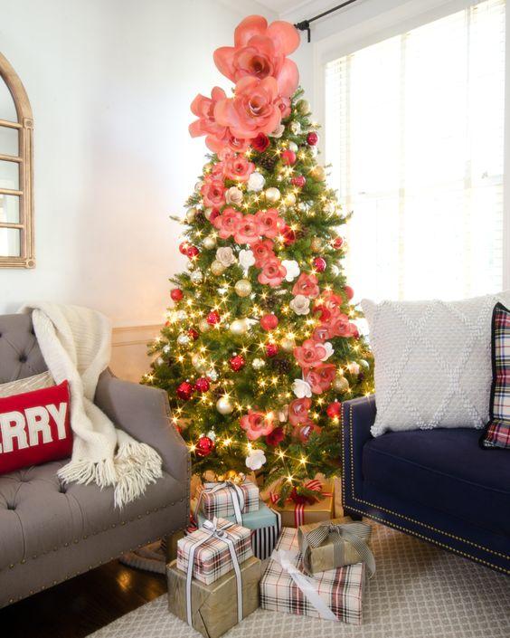 un delizioso albero di Natale con ornamenti d'argento e rossi, fiori finti rosa e bianchi di varie dimensioni è bello e chic
