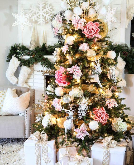 un albero di Natale glam decorato con fiori finti rosa e cipria, palle di neve bianche e cervi più alcune luci