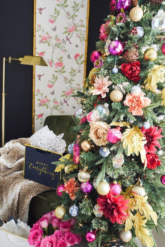 un albero di Natale glam decorato con fiori rosa, rossi, pesca e gialli, foglie, ornamento metallico lucido e audace e pigne