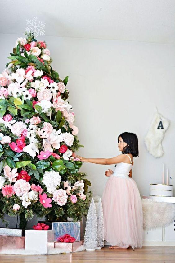 uno splendido albero di Natale decorato con fiori bianchi, blush e rossi e foglie di magnolia più un fiocco di neve
