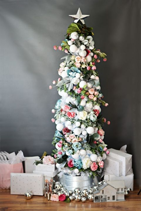 un grazioso piccolo albero di Natale decorato con ornamenti bianchi e argento, blush, fiori rosa e blu e nastri verdi e grigi
