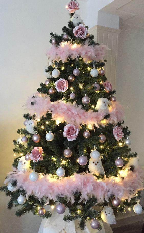 un grazioso albero di Natale con ornamenti bianchi e arrossati, gufi bianchi, ghirlande di piume rosa e luci è molto chic e audace