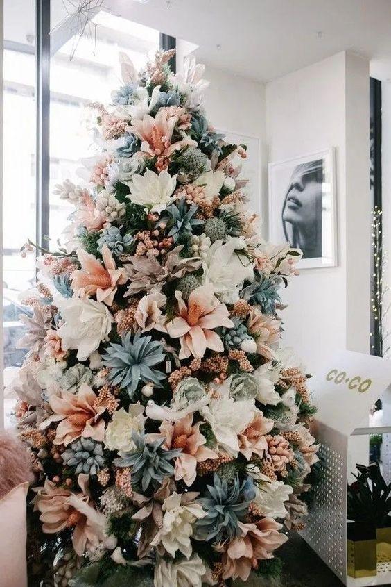 un albero di Natale pastello con fiori bianchi, rosa cipria e blu pallido e alcune ghirlande rosa è un'idea unica da scegliere