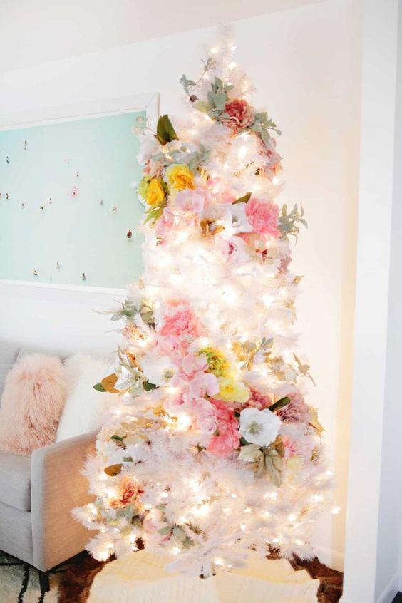 un adorabile albero di Natale bianco con fiori bianchi, rosa, gialli, verde chiaro e luci è un'idea eterea e chic per il rock