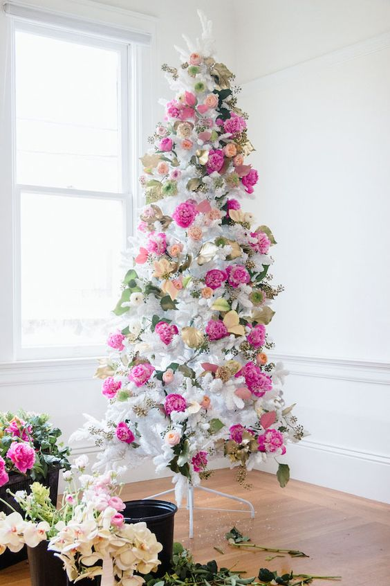 un romantico albero di Natale bianco decorato con fiori rosa caldo e blush, foglie e fogliame dorato è super elegante