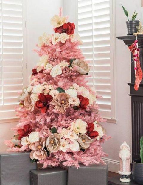 un piccolo albero di Natale rosa decorato con fiori bianchi, neutri, rossi e rosa - finti e naturali per un tocco glam