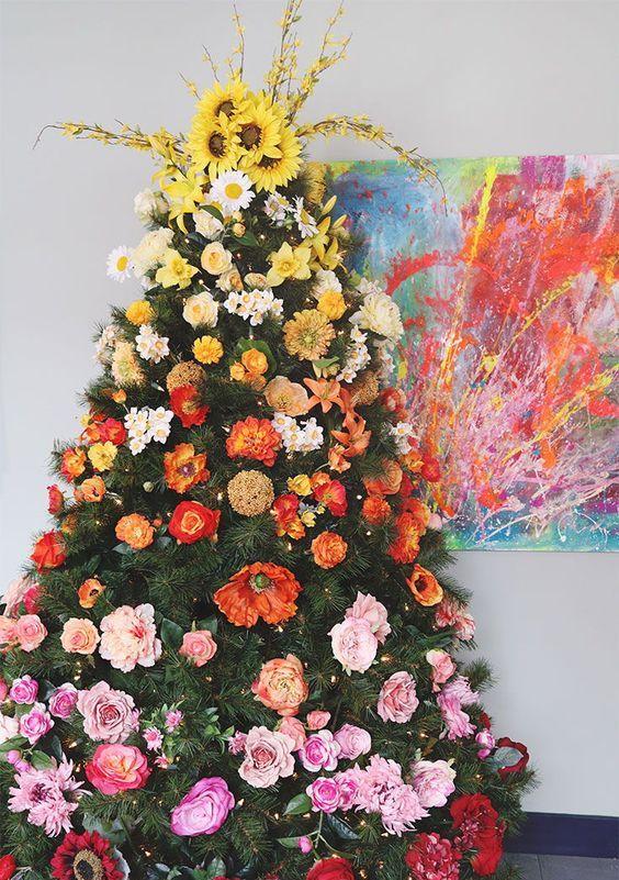 un albero di Natale sfumato super audace decorato con fiori finti dal giallo al rosso intenso e con luci è bellissimo