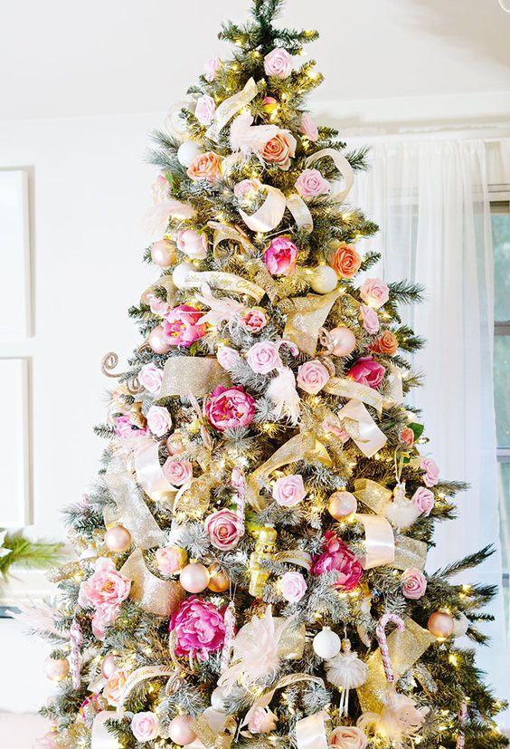 un romantico albero di Natale decorato con nastri a maglie dorate, luci, ornamenti in oro e argento, fiori rosa, blush e rosa shocking