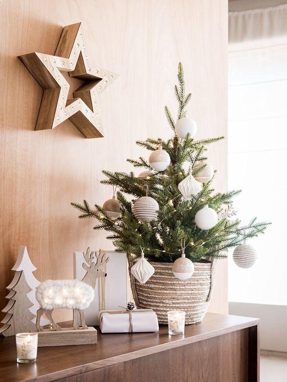 un albero di Natale da tavolo chic con luci, ornamenti oversize marrone chiaro e bianchi oltre a decorazioni in legno per un'atmosfera nordica nello spazio