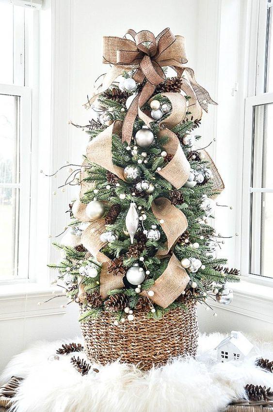 uno splendido albero di Natale da tavolo con ornamenti d'argento, nastri di juta, ghirlande di palle di neve, pigne e un grande fiocco di juta in cima