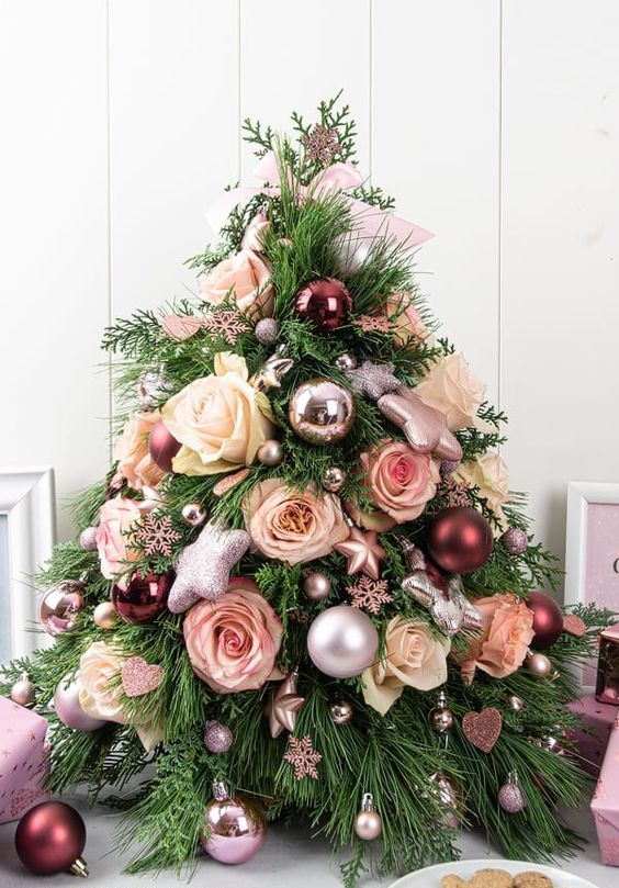 un delizioso albero di Natale da tavolo con rose bianche e blush, sfere metalliche e ornamenti a stella e fiocchi di neve è favoloso
