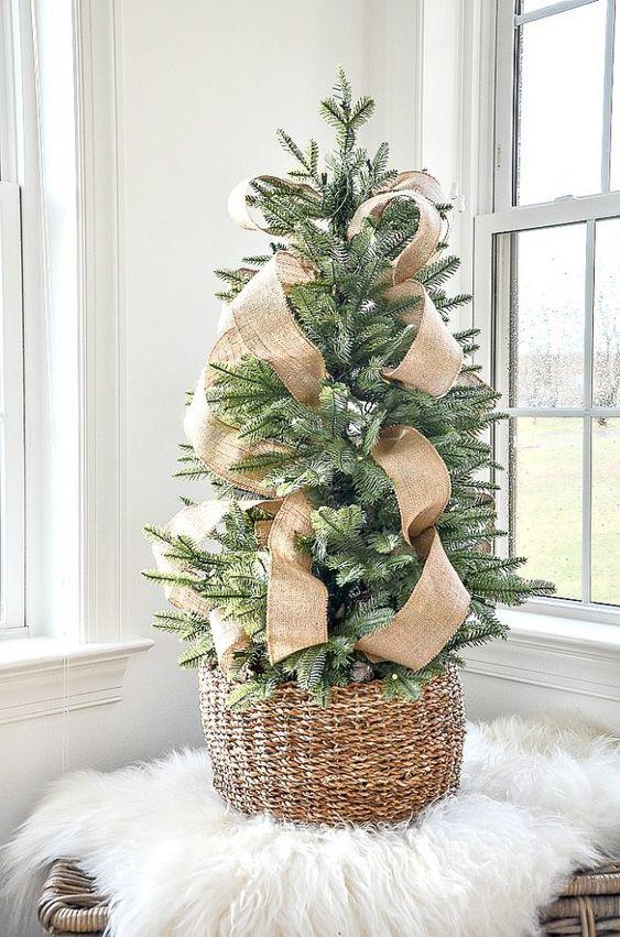 un albero di Natale da tavolo chic e semplice in un cestino con nastri di juta è un'idea adorabile con un tocco rustico leggero ed elegante
