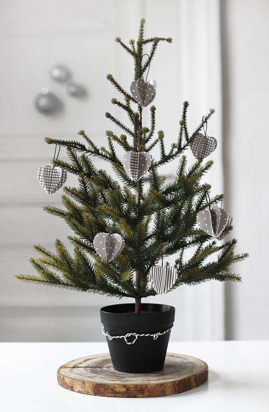 un albero di Natale nordico da tavolo in una pentola decorato con ornamenti di cartone 3D grigi e bianchi è un'idea carina ed ecologica
