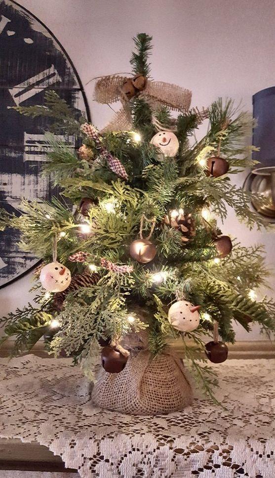 un albero di Natale vintage rustico da tavolo con luci, grandi campane, ornamenti con pupazzo di neve, fiocchi di juta e ghirlande