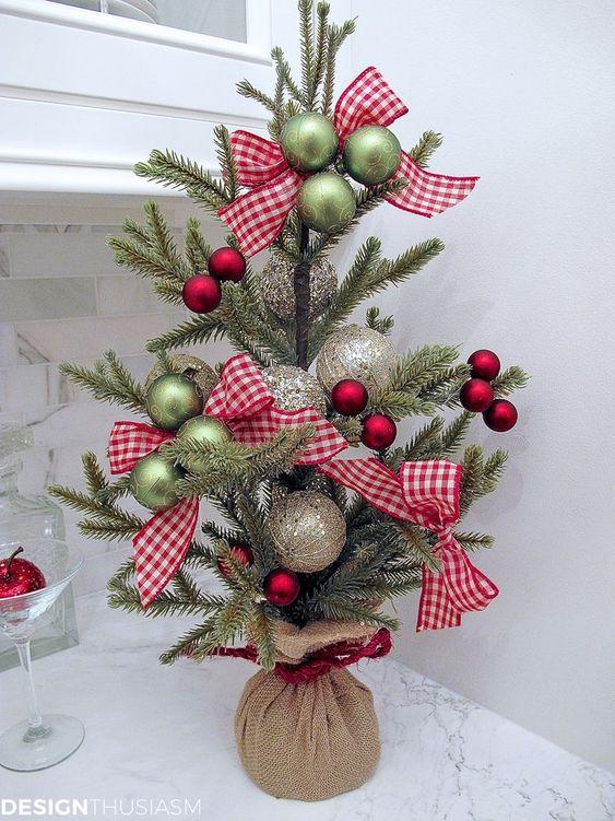 un grazioso albero di Natale da tavolo con ornamenti metallici verdi, rossi e lucenti e fiocchi scozzesi più un sacco di iuta per un tocco rustico