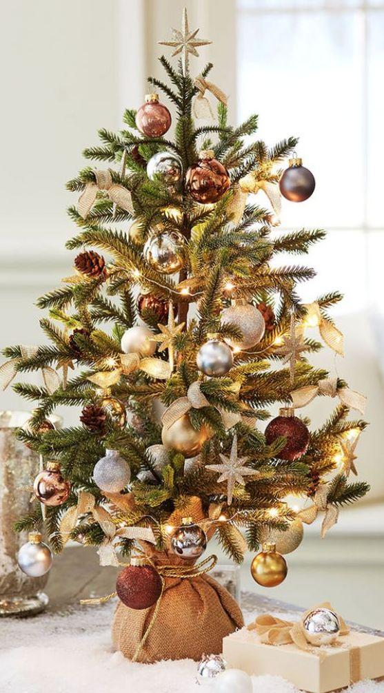 un grazioso albero di Natale da tavolo con luci, ornamenti d'oro e d'argento, pigne e tocchi di rame avvolti in tela da imballaggio