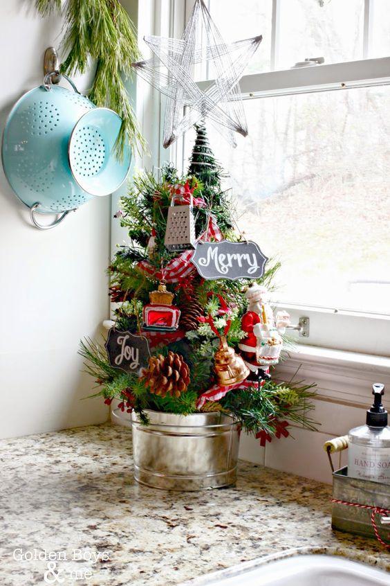 un grazioso albero di Natale da tavolo decorato con pigne e mini elettrodomestici da cucina, le bacche in un secchio è una deliziosa idea vintage