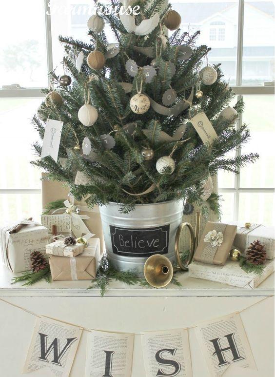 un rustico albero di Natale vintage da tavolo decorato con lavagna e spago e ornamenti avvolti in tela, con stampe di chiavi vintage e alcune pigne intorno