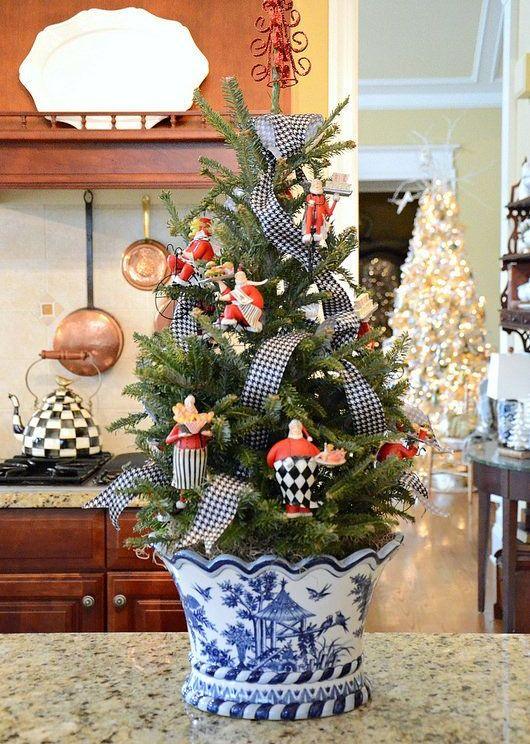 un albero di Natale da tavolo in una fioriera cinese, decorato con nastri stampati e giocattoli vintage è un'idea bella e interessante