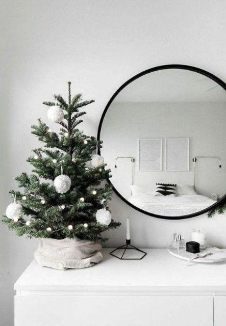 un piccolo e semplice albero di Natale da tavolo con ghirlande di pompon e grandi ornamenti con pompon per un'atmosfera nordica